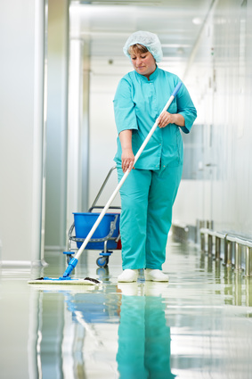Adult cleaner maid woman with mop and uniform cleaning corridor pass floor of pharmacy industry factory or clinic
